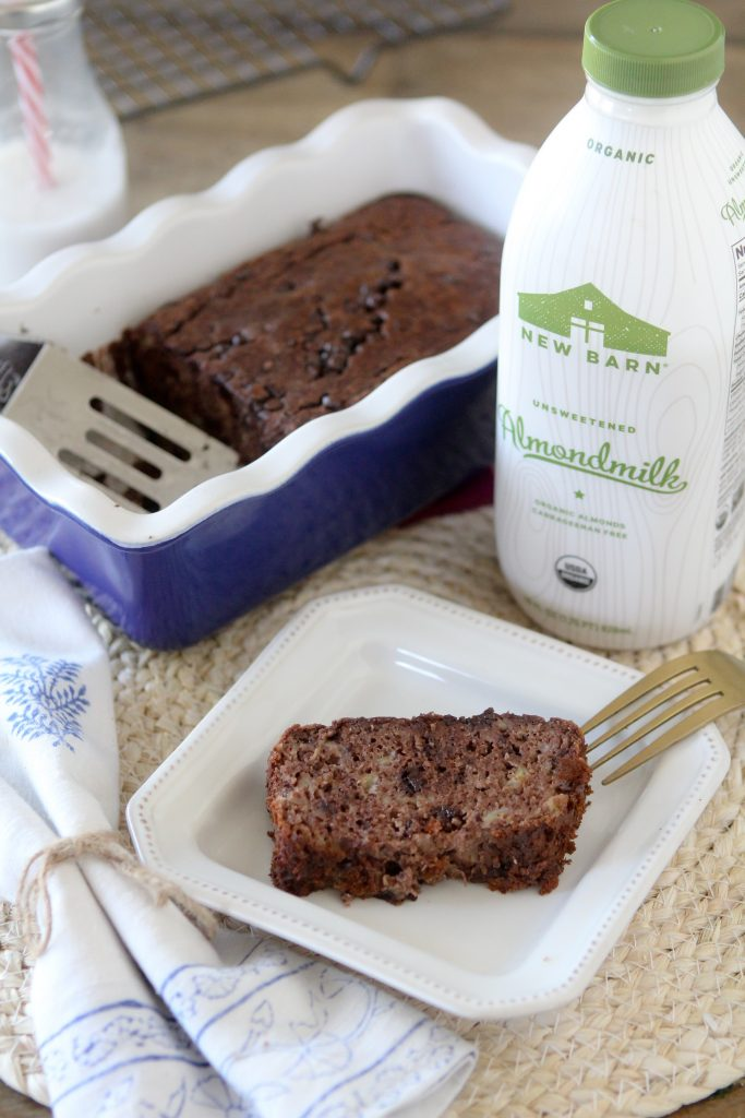 A slice of grain-free Paleo Chocolate Banana Bread with the remaining loaf on the side