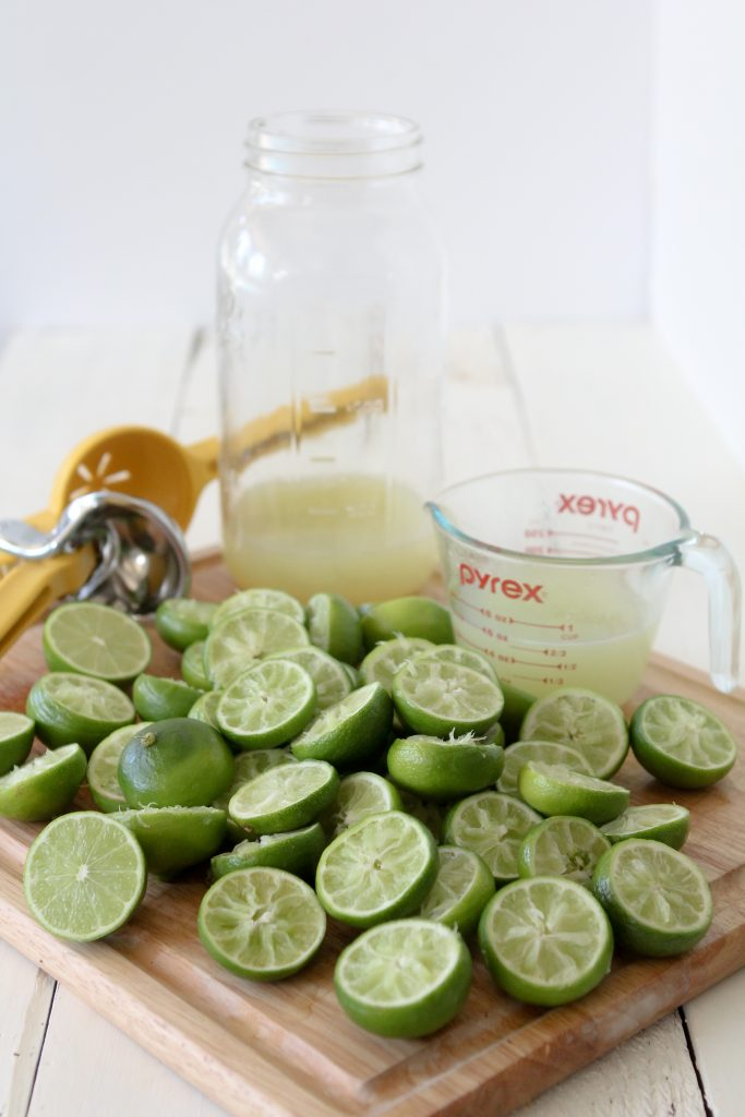 a pile of squeezed out limes on a wooden cutting board