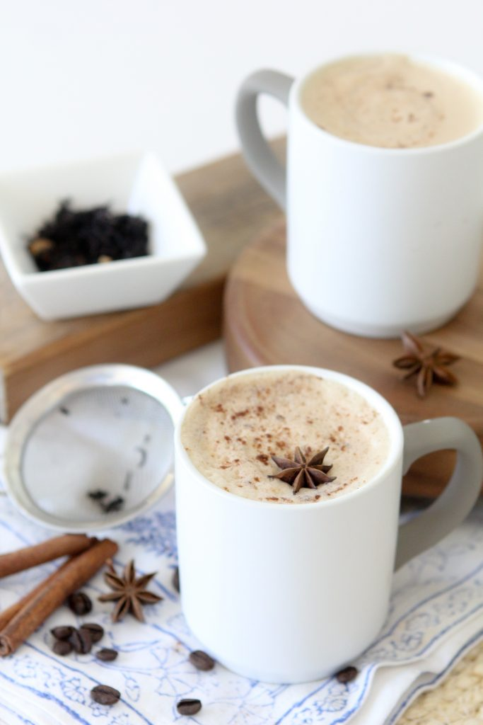two mugs of dirty chai latte topped with with almond milk foam and decorated with star anise
