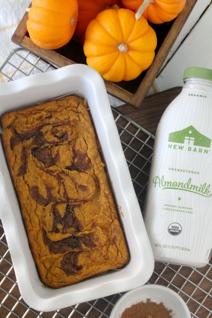 overhead shot of a healthy Pumpkin Bread with cinnamon swirl in a white ceramic loaf pan