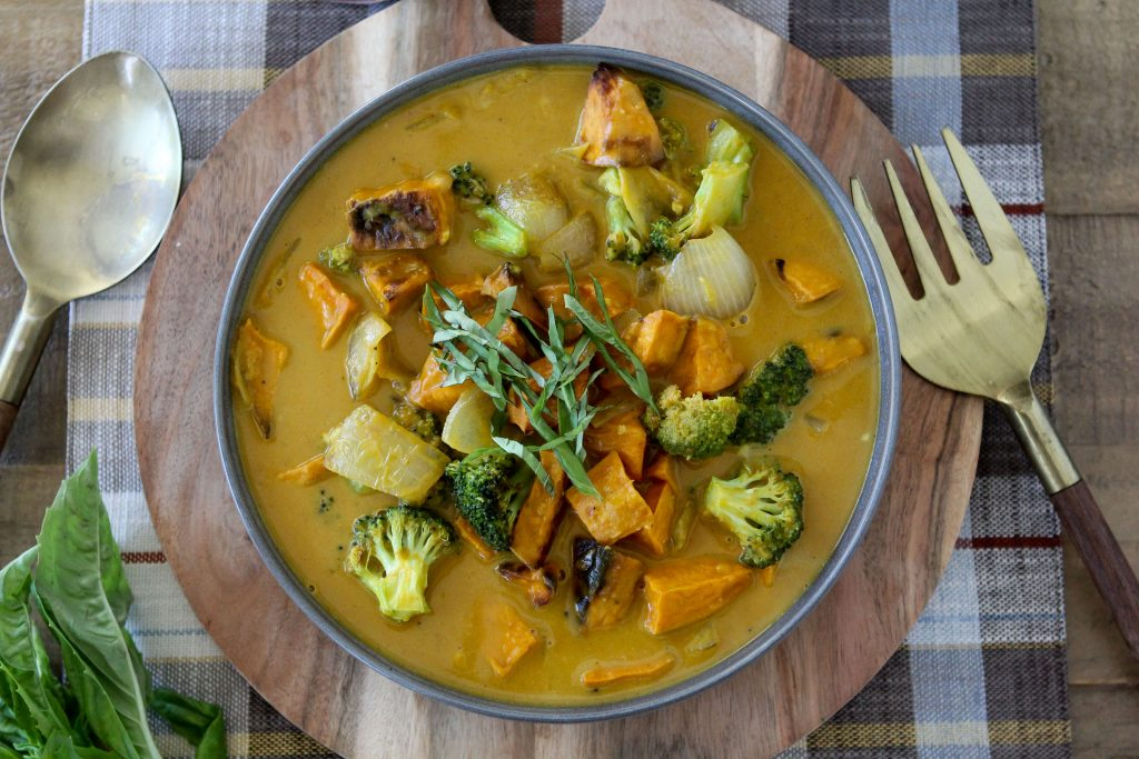 Vegan Pumpkin Curry with chunks of roasted sweet potatoes served in a blue bowl placed on a wooden board