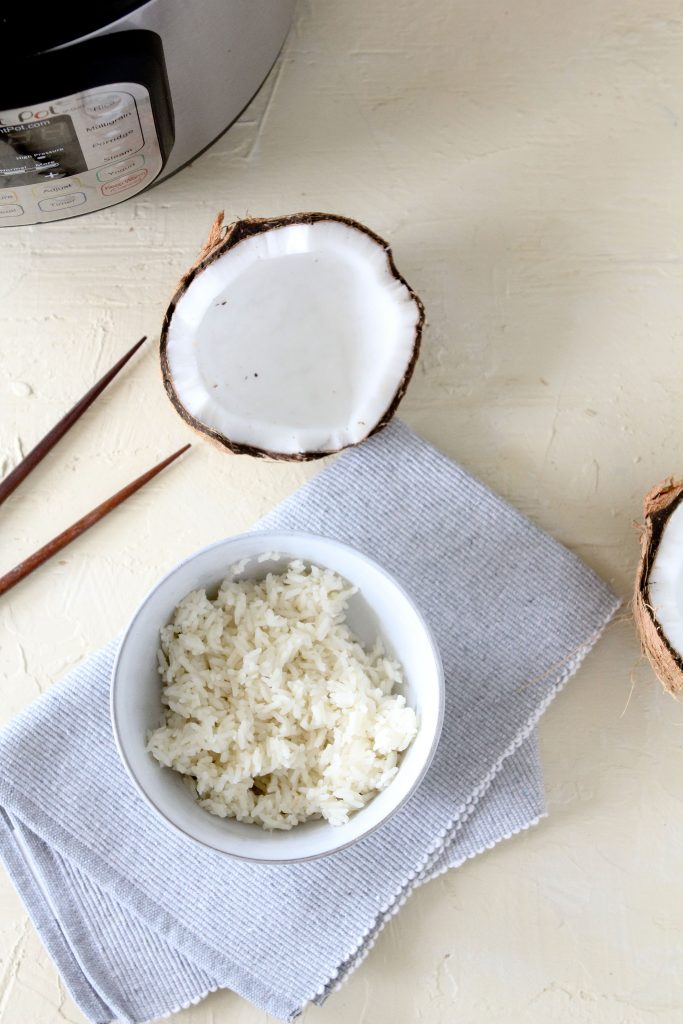 overhead shot of a small bowl with homemade Instant Pot Coconut Rice and a halved coconut