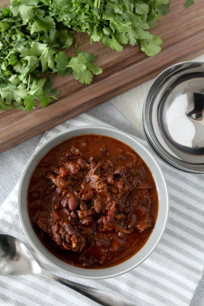 overhead shot of a bowl of Instant Pot Short Rib Chili on a striped tablecloth