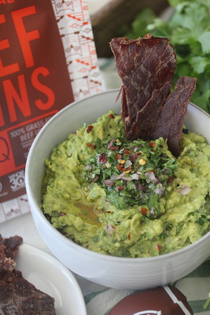 a bowl of guacamole served with beef jerky for dipping