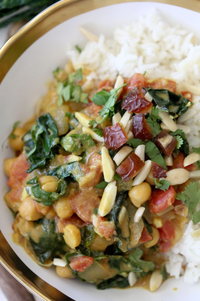 close-up of a bowl of vegan kale and chickpea curry served over fluffy white rice