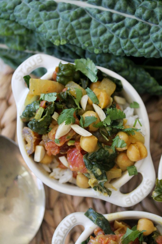overhead shot of a small white casserole dish with healthy vegan chickpea curry with kale