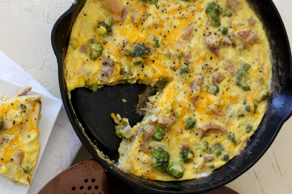 overhead shot of a healthy broccoli chicken cheddar fritatta in a black skillet