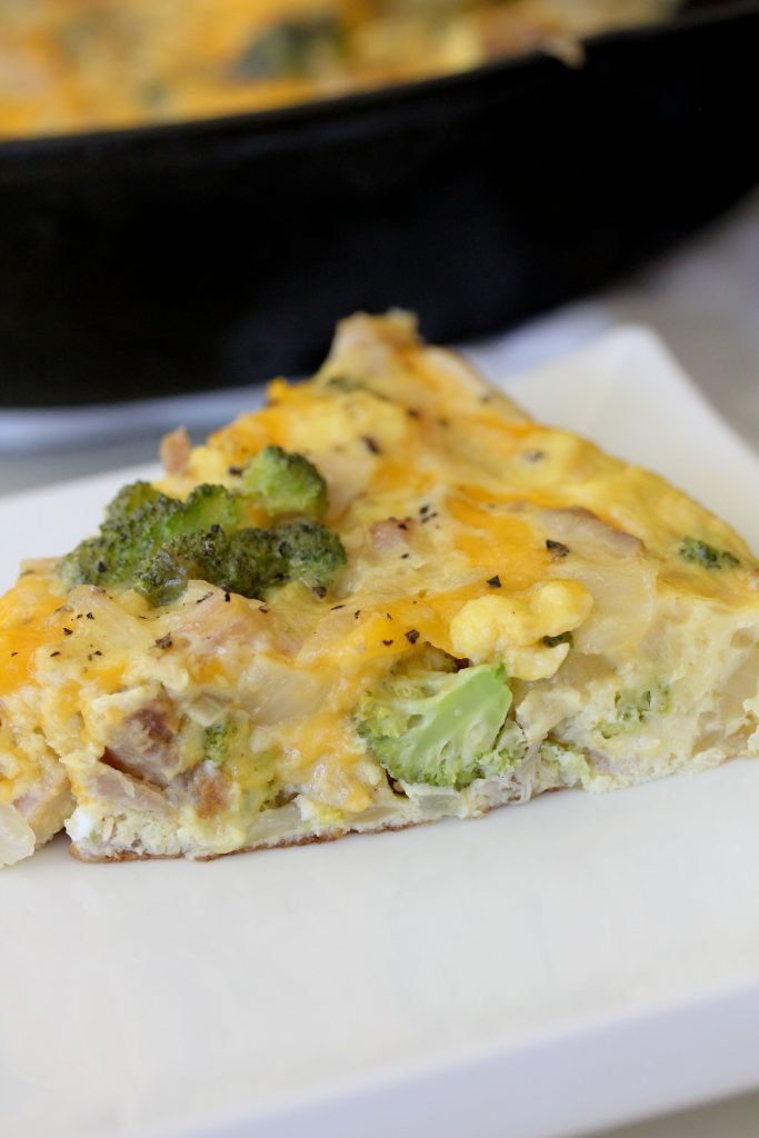 close-up side view of a piece of healthy frittata with broccoli chicken and cheddar on a white plate