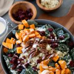 overhead shot of a quinoa harvest bowl with roasted sweet potatoes, kale, pecans and blue cheese drizzled with tahini dressing