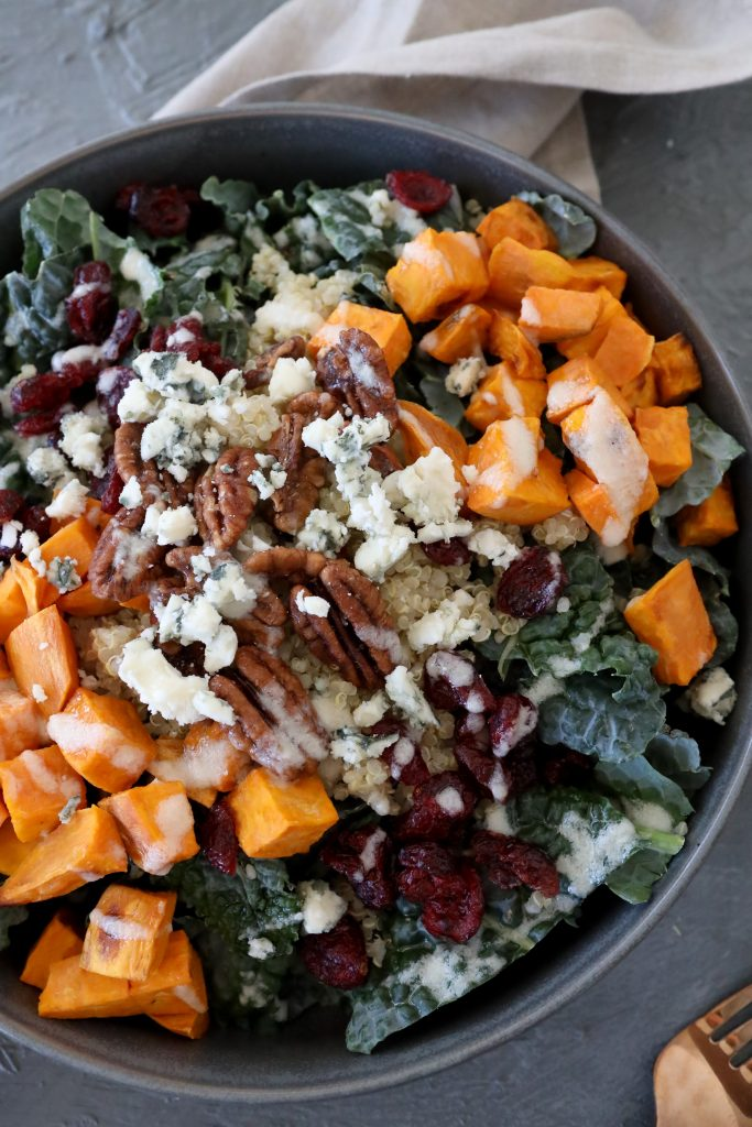 close-up of a healthy glutenfree harvest bowl with quinoa, kale, sweet potatoes, blue cheese and tahini dressing