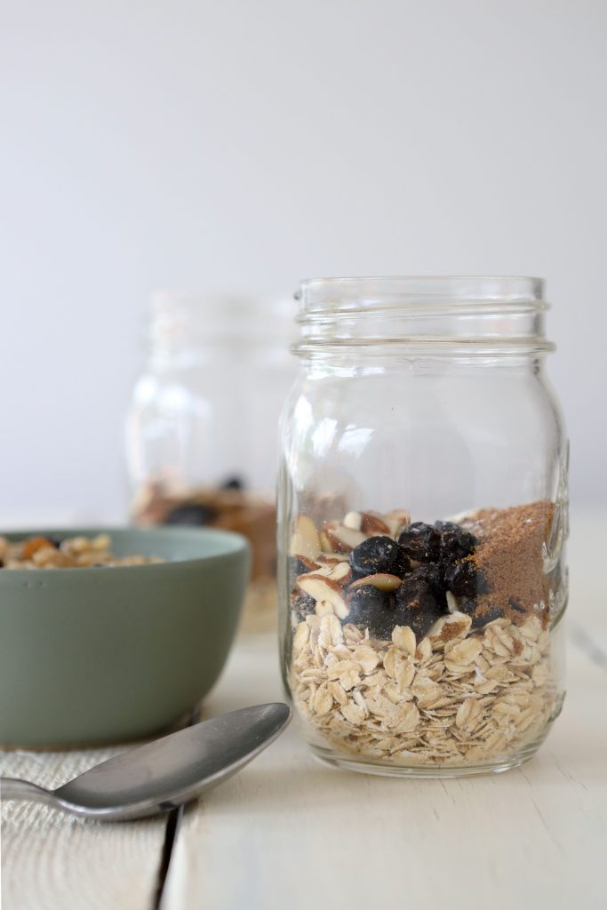 side view of a meal prep mason jar filled with oatmeal, collagen powder and dried blueberries