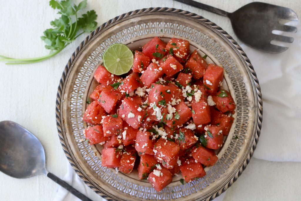 a big metal plate with chili lime watermelon salad topped with queso fresco and chopped herbs