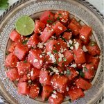 chili lime watermelon salad topped with queso fresco on a metal plate