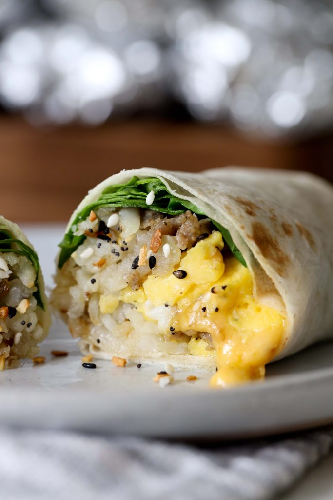 side view of a halved healthy gluten-free everything bagel breakfast burrito with sausage and cheese