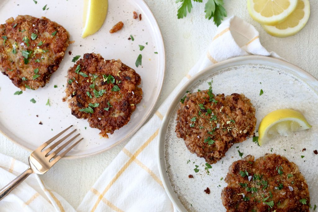 two servings of pork schnitzel decorated with lemon wedges and parsley
