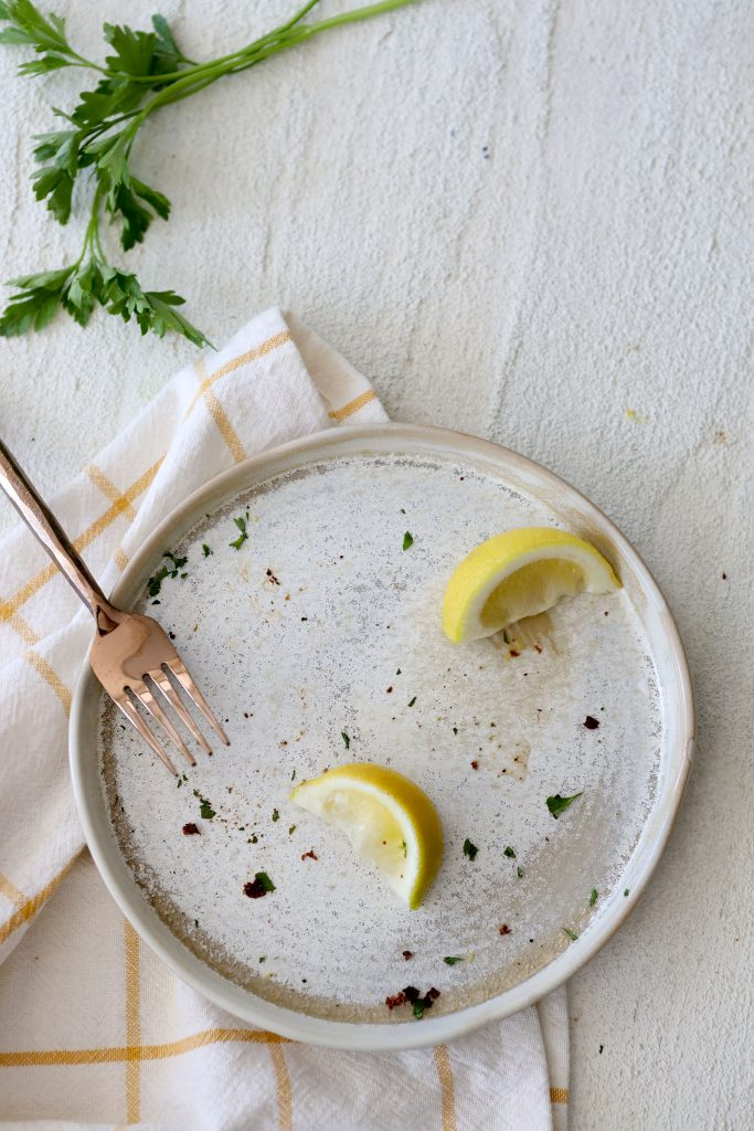 an empty plate with lemon wedges and parsley